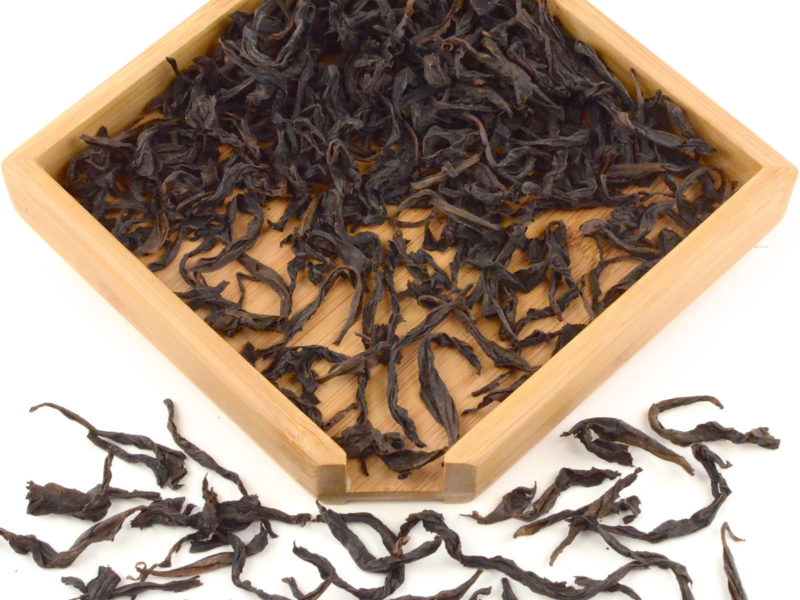 Laocong Shuixian rock wulong tea dry leaves in a wooden display box.