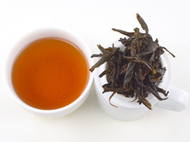 Cupped infusion of Laocong Shuixian rock wulong tea and strained leaves.