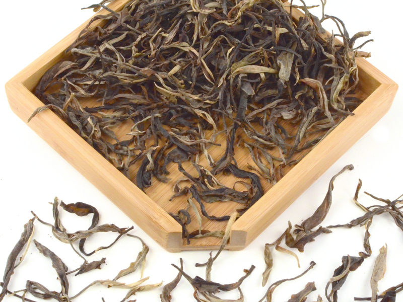 Daxueshan (Snow Mountain) sheng puer tea dry leaves in a wooden display box.
