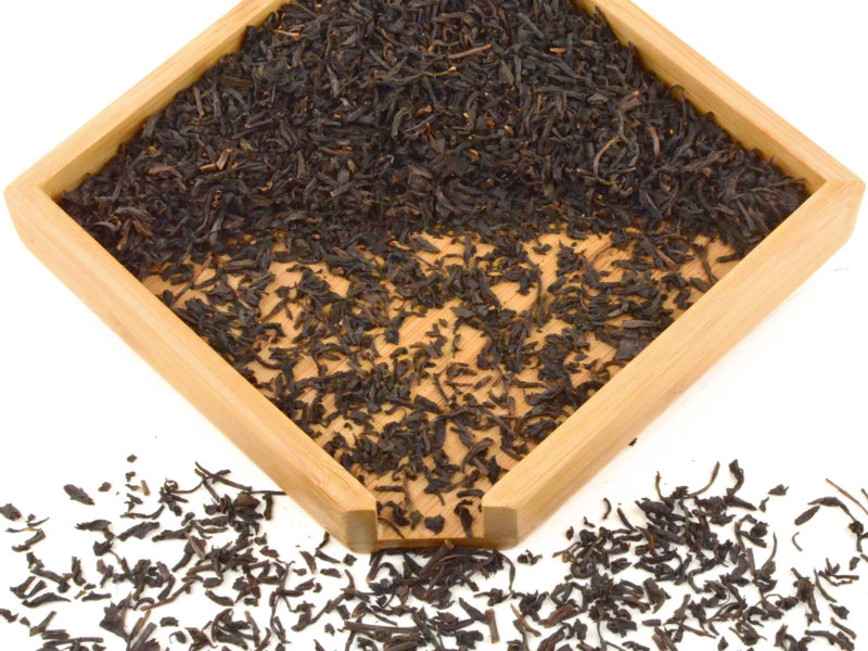 Lapsang Souchong black tea dry leaves in a wooden display box.