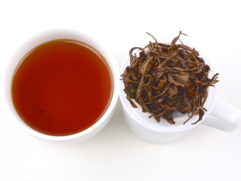 The rich red infusion and wet leaves of brewed Jin Kong Que Golden Peacock black tea.