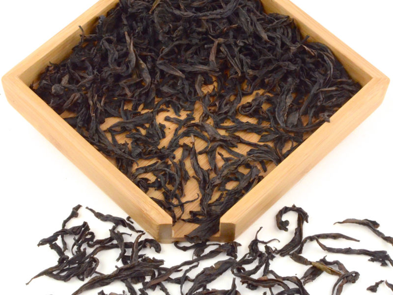 Xiao Hong Pao rock wulong tea dry leaves in a wooden display box.
