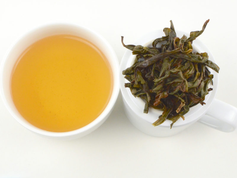 Cupped infusion of Yu Lan Xiang (Magnolia) wulong tea and strained leaves.