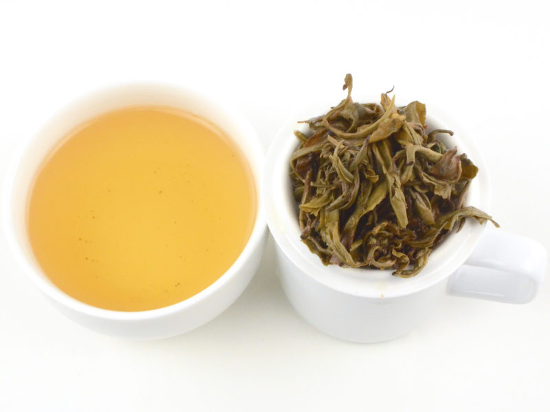 Cupped infusion of Moli Longzhu (Jasmine Pearls) scented green tea and strained leaves.