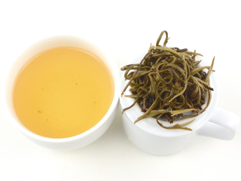Cupped infusion of Yinhao Longzhu (Silver Dragon Jasmine Pearls) scented green tea and strained leaves.