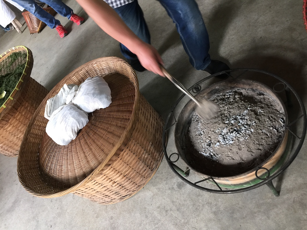 A woven bamboo drum with small bundles of fabric-wrapped tea on top, next to a round charcoal brazier smothered with ash.