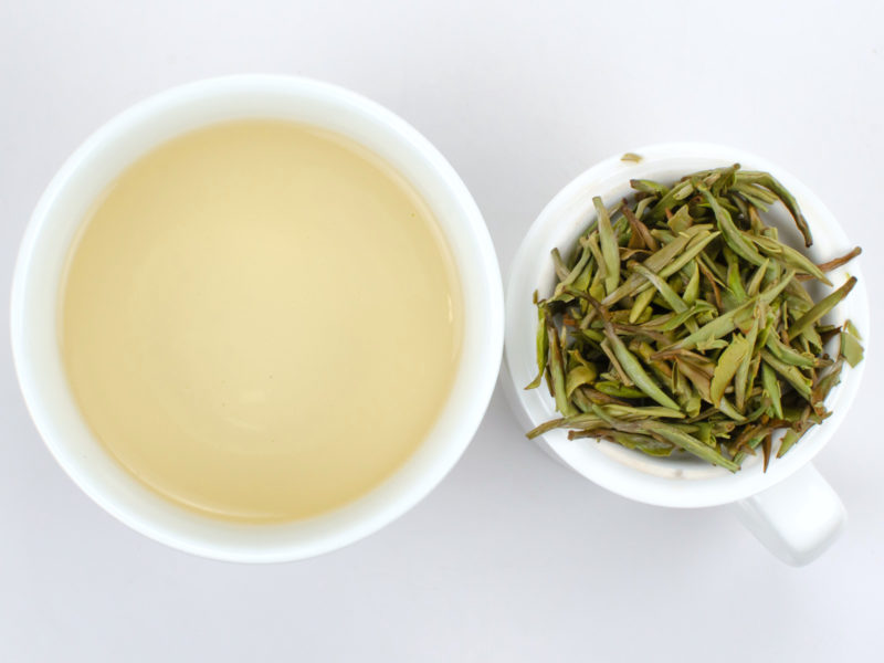 Cupped infusion of Baihao Yinzhen tea and strained leaves.