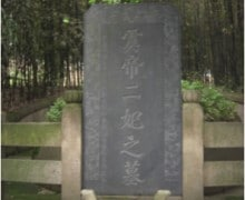 A tall inscribed tombstone in a forested area.