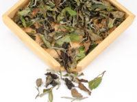 Bai Mudan (White Peony) dry white tea leaves displayed on a bamboo tray.