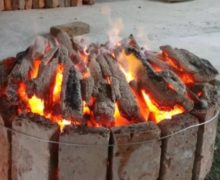A blazing open-flame circular charcoal brazier used for roasting Lu