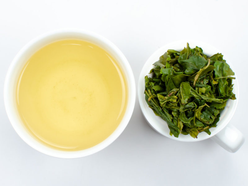 Cupped infusion of Lu'an Gua Pian green tea and strained leaves.