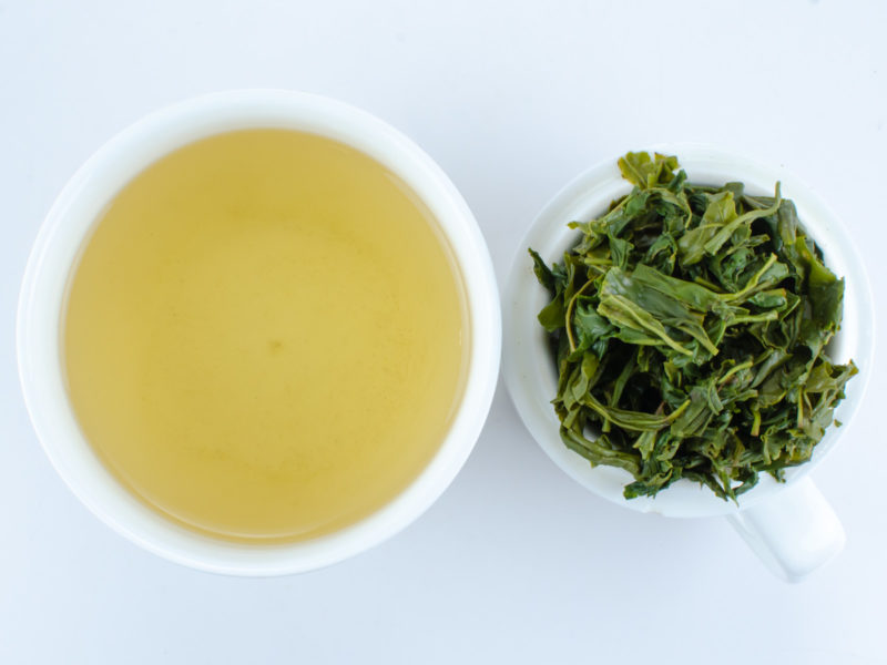 Cupped infusion of Yun Wu green tea and strained leaves.