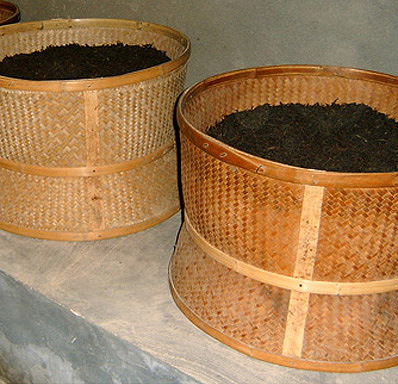 Two large woven bamboo drums filled with rock wulong tea, set over top of a recessed charcoal stove to roast.