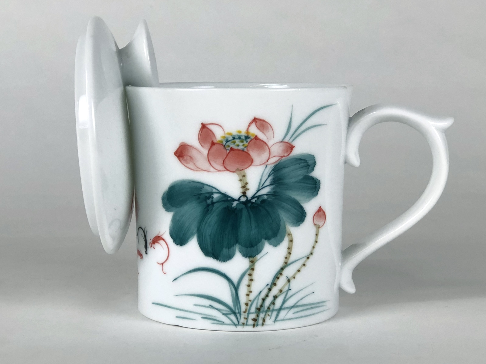 Tea mug with lotus painting and strainer built into its wall