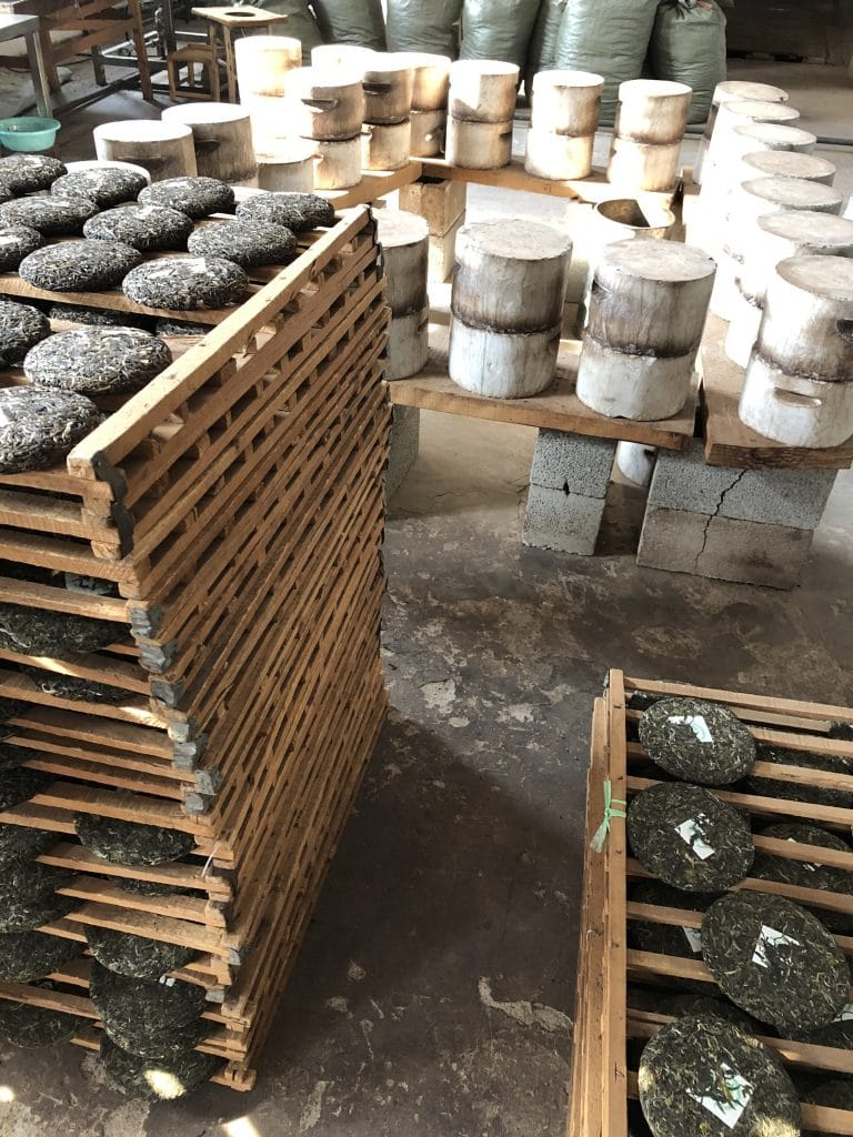 Completed puer cakes on their drying racks sit next to stone compression molds.