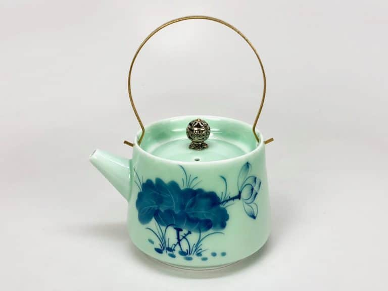 A lotus leaf iron handle small porcelain pot, about as tall as it is wide, with a tall, curved overhead handle. The body of the pot is largely cylindrical, with the base slightly larger than the top.