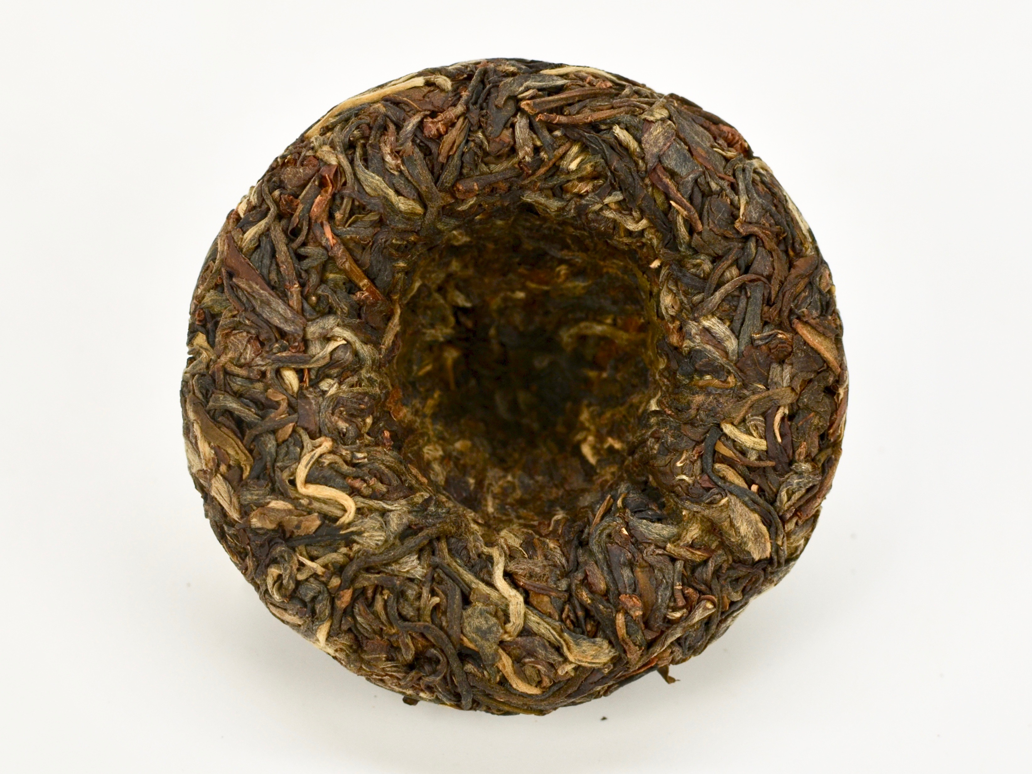 A round Little Sheng Tuocha 2014 Sheng Puer Cake unwrapped to show the compressed tea leaves in shades of dark green and the deep indentation in the center of the back of the puer cake.