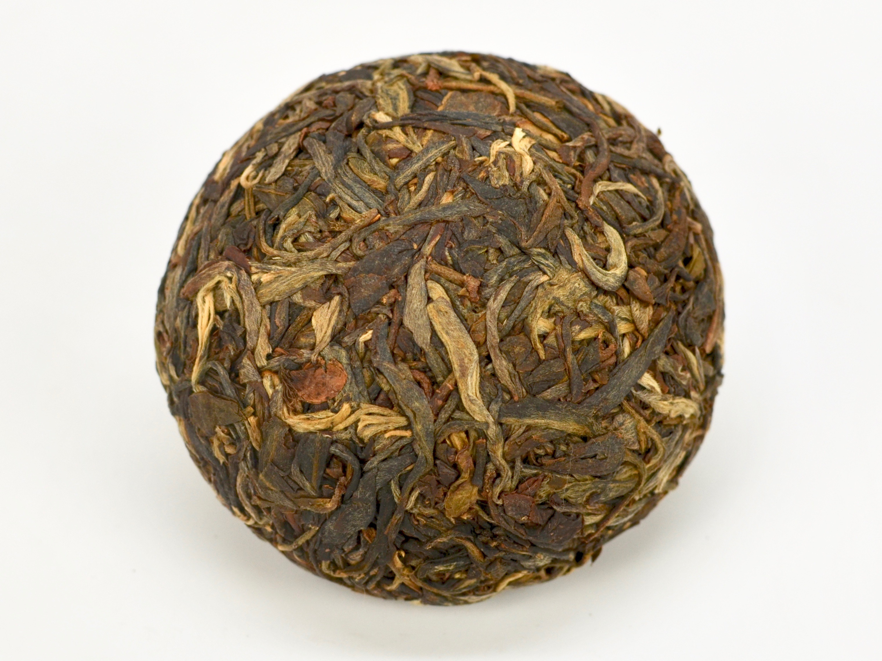 A round Little Sheng Tuocha 2014 Sheng Puer Cake unwrapped to reveal the compressed tea leaves in shades of dark green.