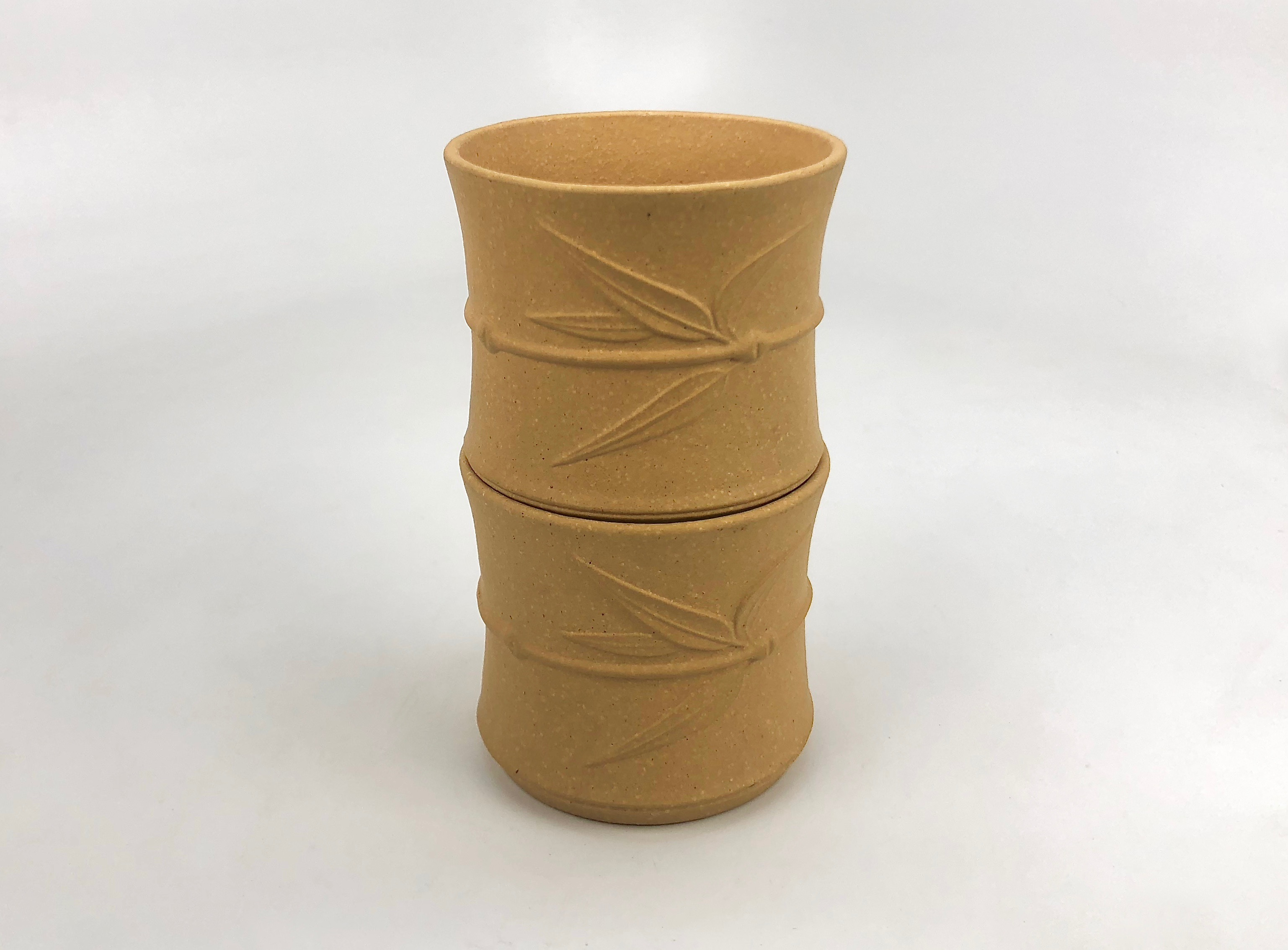 Two bamboo leaf yellow yixing clay cups stacked one on top of the other. The bamboo segment shape of each cup makes the stack appear to resemble a growing bamboo stalk.