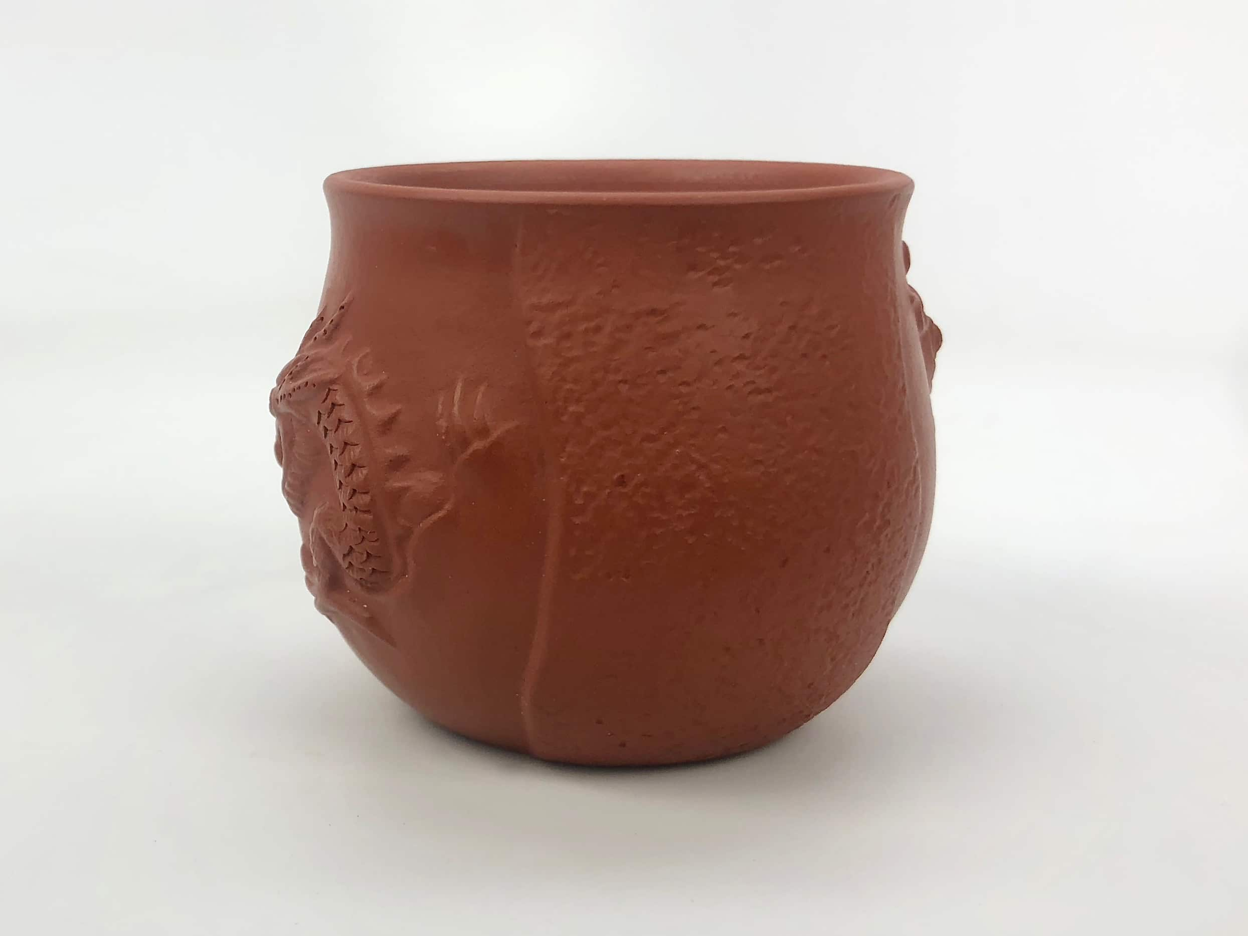 A rounded, slightly fluted dragon and fish red yixing clay cup. The raised cloud pattern in between the dragon and fish is slightly textured.