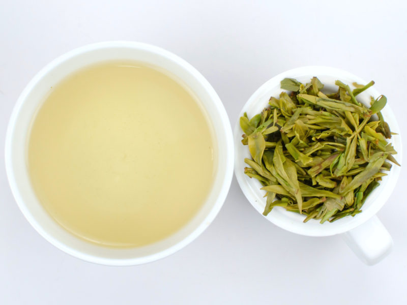 Cupped infusion of Shifeng Longjing and strained tea leaves.
