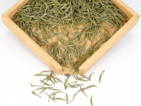Junshan Yinzhen dry yellow tea leaves displayed on a bamboo tray.