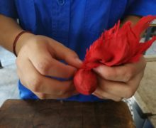 A worker holding a single serving of Sweet Dragon Ball Shu Puer wrapped in red fabric, being shaped by hand.