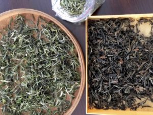 Two different years of Bai Mu Dan white tea leaves side by side. The fresh is green and white and the aged is brown.