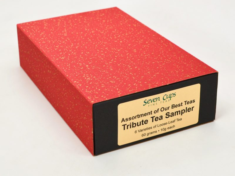 The closed decorative cardboard box of the Tribute Tea Sampler, red and gold on the outside with a black base.