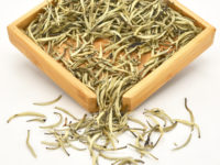 White Dragon Whiskers dry tea leaves in a wooden display box.