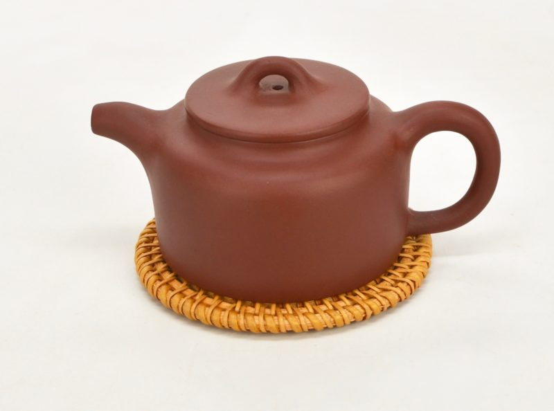 Dark brown cattle bell yixing clay pot on top of big rattan tea saucer