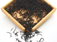 Anji Hong black tea dry leaves in a wooden display box.