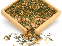 Xuanmicha (Genmaicha) green tea dry leaves and rice grains in a wooden display box.