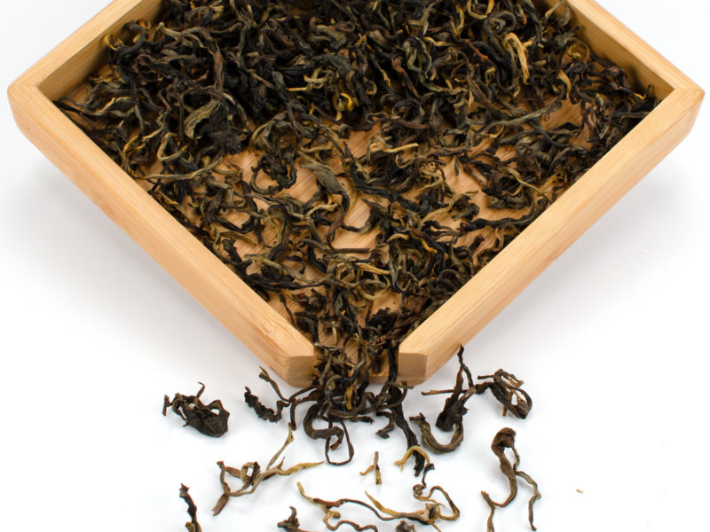 Youle Xiaoshu (Youle Young Tree) black tea dry leaves in a wooden display box.