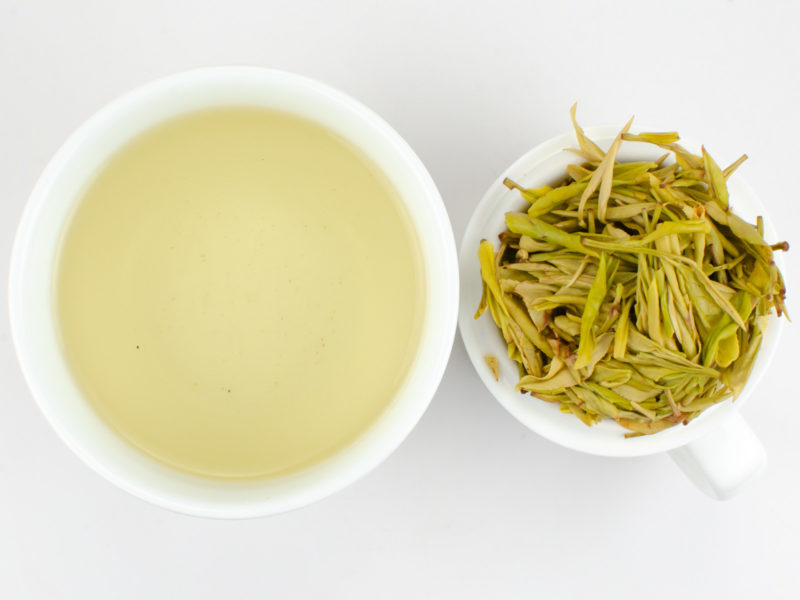 Cupped infusion of Huang Jin Ye (Golden Leaf) green tea and strained leaves.