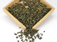 High Mountain Tieguanyin Anxi wulong tea dry leaves in a wooden display box.
