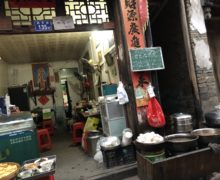 Looking into the tiny cluttered kitchen of a streetside tofu restaurant.