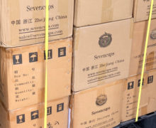 Stacked cardboard shipping boxes of tea with the Seven Cups company logo on the side, lashed to a pallet. 2020.